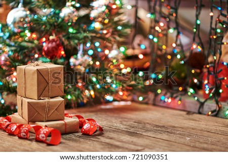 Gift gift boxes with a large red bow against a background bokeh of twinkling party lights negle Images
