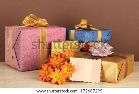 Gift boxes with blank label and flowers on table on brown background