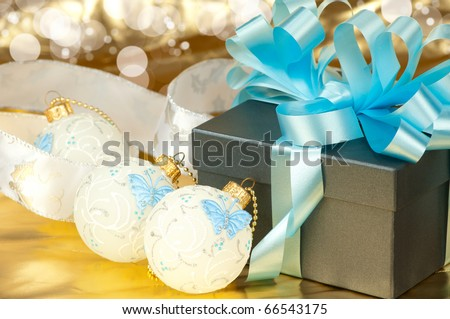 Gift boxes with blue ribbon and christmas toys on golden background - stock photo