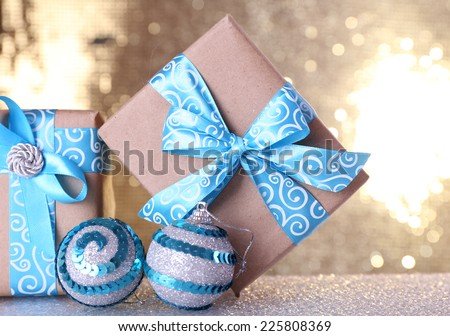 Gift boxes with blue ribbon and Christmas tree toy on table on shiny background - stock photo