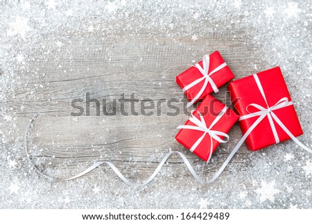 Gift boxes with bow and snowflakes on wooden background - stock photo
