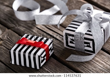 Gift boxes with curved silver ribbon on old wooden background. - stock photo