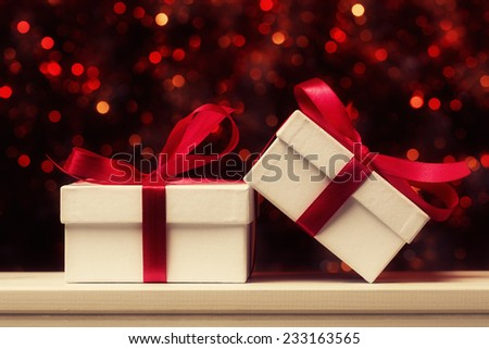 Gift boxes with red bow against defocused lights - stock photo