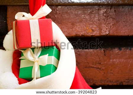Gift boxes with ribbon in a Christmas sock hanging on fireplace mantel - stock photo
