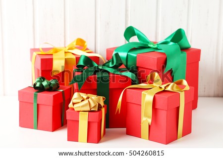 Gift boxes with ribbon on white wooden table
