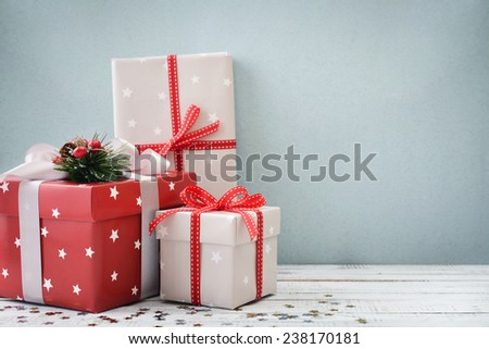Gift boxes with ribbons and christmas decor on wooden background - stock photo
