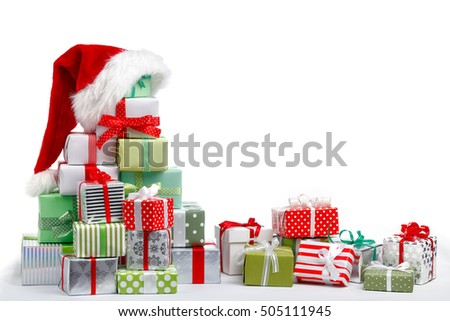 Gift boxes with Santa Claus hat on white background