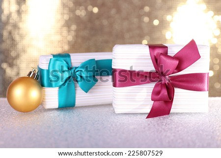 Gift boxes with vinous and blue ribbons and Christmas tree toy on table on shiny background - stock photo