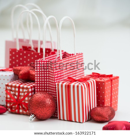 Gift boxes with xmas presents wrapped in red paper with ornament - stock photo