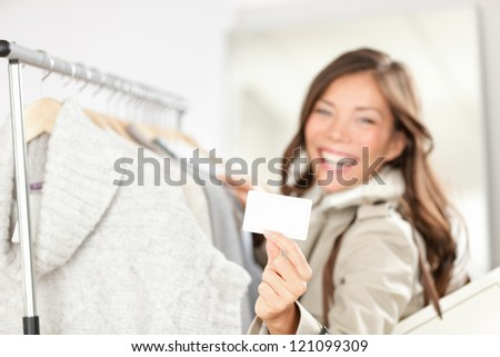 Gift card woman shopping clothes. Happy shopper holding showing gift card or business card in store while shopping for clothing. - stock photo