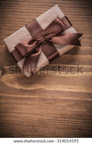 Gift container with brown bow on vintage wooden board.