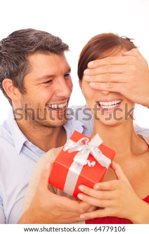 Gift couple holding present closing someone eyes - stock photo