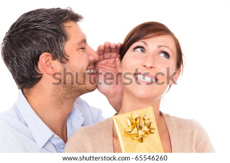 Gift couple holding present whispering ear - stock photo