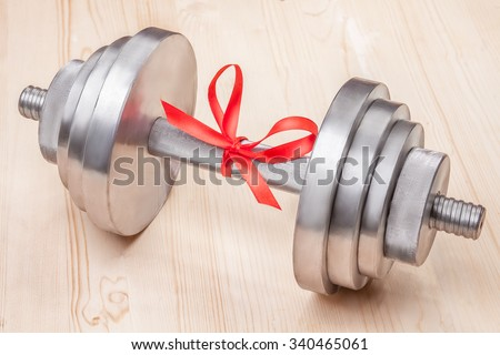 gift - dumbbell tied with red ribbon on wooden desk - stock photo