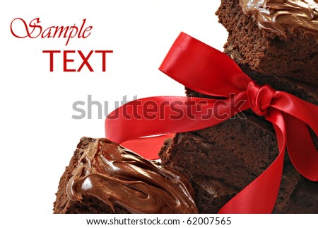 Gift for chocolate lovers.  Freshly baked brownies with red satin ribbon on white background with copy space.  Macro with shallow dof. - stock photo
