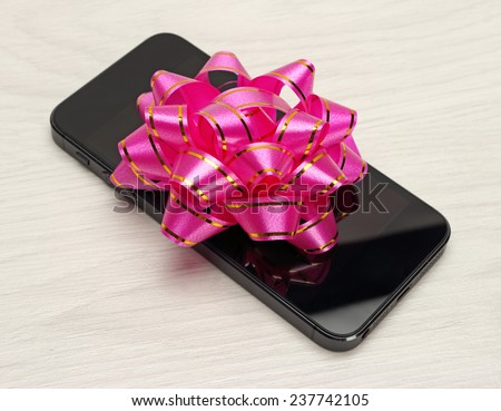 Gift for the holidays phone with a bow - stock photo