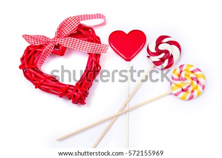 Gift for Valentines day. Red wooden heart and different lollipops on the white background.