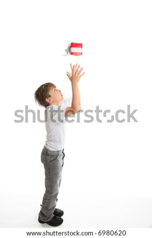 Gift from Heaven.   A wrapped present drops into a boys hands from above.  concept. - stock photo