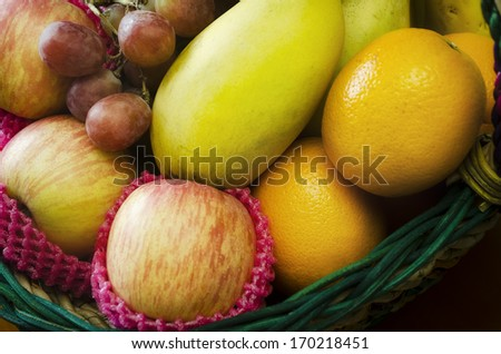 Gift fruit basket filled with grapes, apples, mangoes, and oranges - stock photo