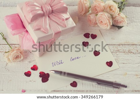 Gift, hearts, flower and greeting card on wooden background in vintage style, selective focus - stock photo