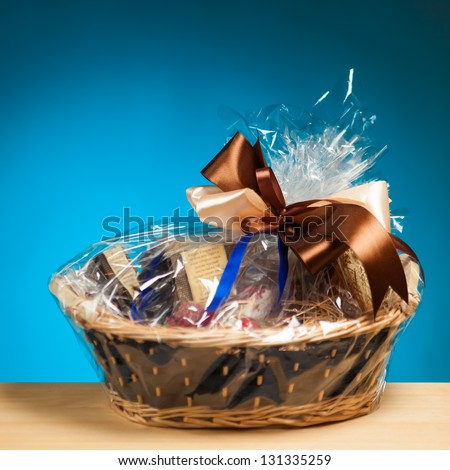 gift in a basket against blue background - stock photo