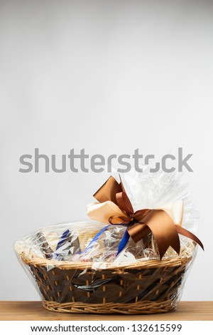 gift in a basket, grey background - stock photo