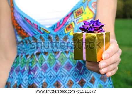 Gift in womans hand. outdoor. - stock photo