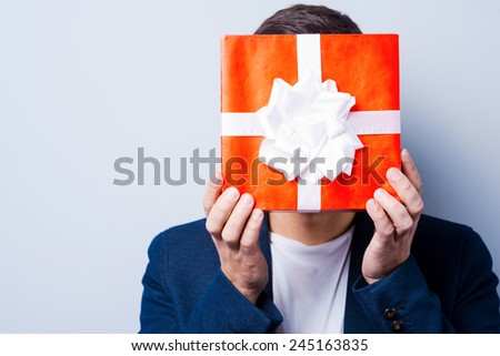 Gift man. Close-up of young man in formalwear covering his face by a gift while standing against grey background - stock photo
