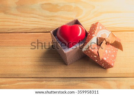 Gift of love. hearty gift. A gift box with a red heart inside. On the wooden floor