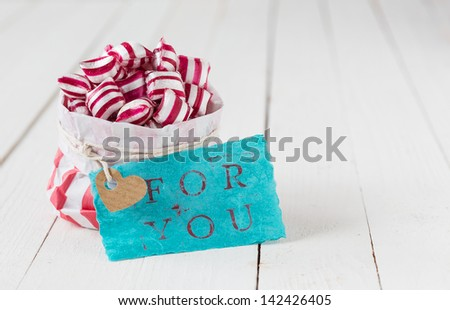 Gift of red and white striped candy in a paper packet with a blue tag with the words For You on a background of white wooden boards - stock photo