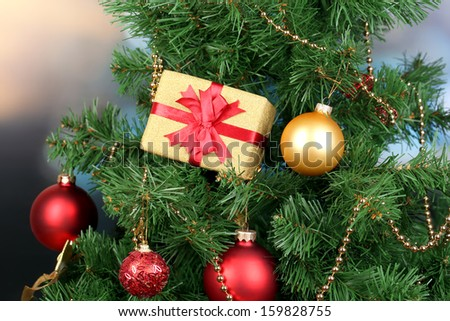 Gift on Christmas tree on room background