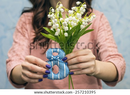 Gift on March 8. Girl holding lily of valley, close-up - stock photo