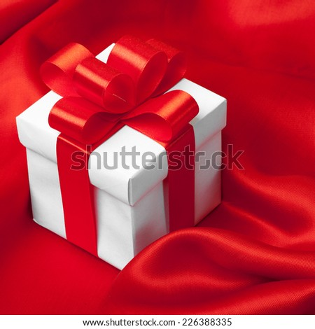 gift on red satin background. studio shot - stock photo