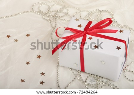 Gift on white silk background. - stock photo