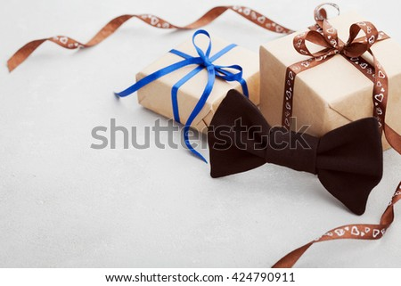 Gift or present box with ribbon and bowtie on gray desk for Happy Fathers Day, copy space for your text or design - stock photo