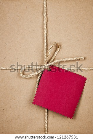 Gift package and red card in brown paper wrapper tied with string close up