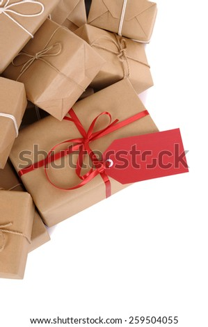 Gift package : pile of brown parcel, red tag isolated, vertical - stock photo