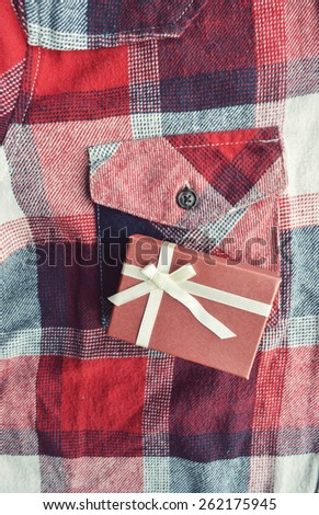 gift packed in a pink box on a red background, close-up - stock photo