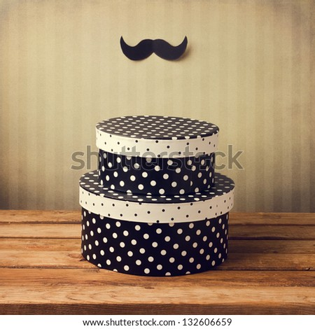 Gift polka dots boxes with mustache decoration - stock photo