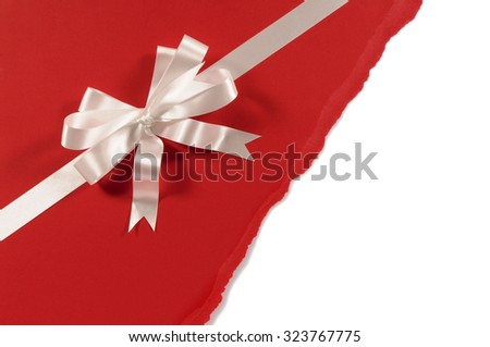 Gift ribbon bow in white satin on untidy torn red paper background - stock photo