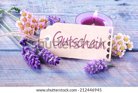 Gift tag with the word Gutschein in German on light blue wooden boards with a burning candle and scented lavender and fresh flowers in a spa and wellness concept - stock photo