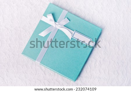 Gift turquoise box with white satin ribbon on lace tablecloth - stock photo