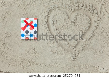 Gift with bow next to heart shape symbol on sand.