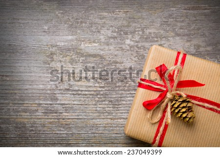 Gift with red bow on wooden defocused background - stock photo