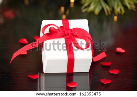 gift with red ribbon on the table with hearts - stock photo