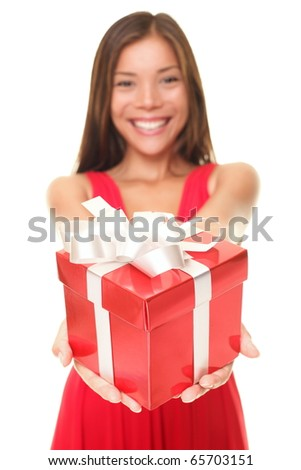 Gift woman in red giving present smiling to camera. Beautiful mixed Caucasian / Asian model isolated on white background. Shallow depth of field, focus on gift.