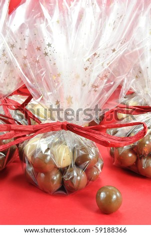 Gift wrapped bags of chocolate balls on red background - stock photo