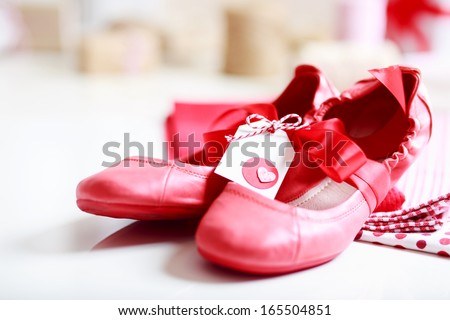 Gift wrapped girls red shoes with ribbon and heart tag - stock photo