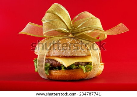 Gift wrapped hamburger , conceptual food image with red background - stock photo