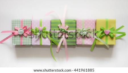 Gift wrapped in paper. Small gifts are packed in colored paper. Colored ribbons. Gift wrapping. View from above. Pastel shades. Rose petals crimson.